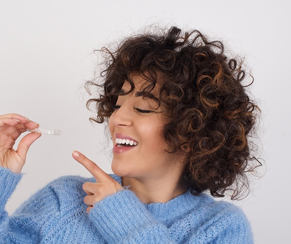 A young woman wearing a blue sweater smiling and pointing to her clear aligner that she's holding in her right hand