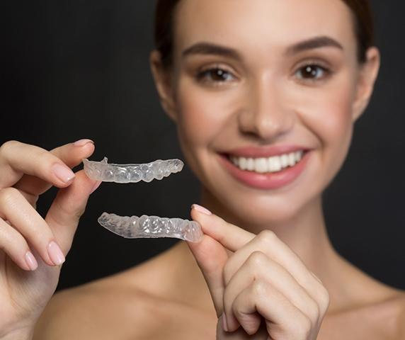 A young female holds a clear aligner in one hand and a mouth mold with traditional braces in the other hand