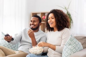 couple watching a movie and smiling with veneers